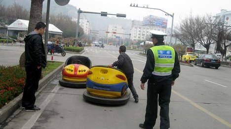 китаец электромобиль дорога, китаец на электромобилях, китаец на двух машинах, Man Driving Two Bumper Cars Down The Street In China